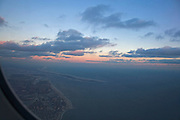 view of airplane during a beautiful sunset sunrise flying over coastal Long Island NY