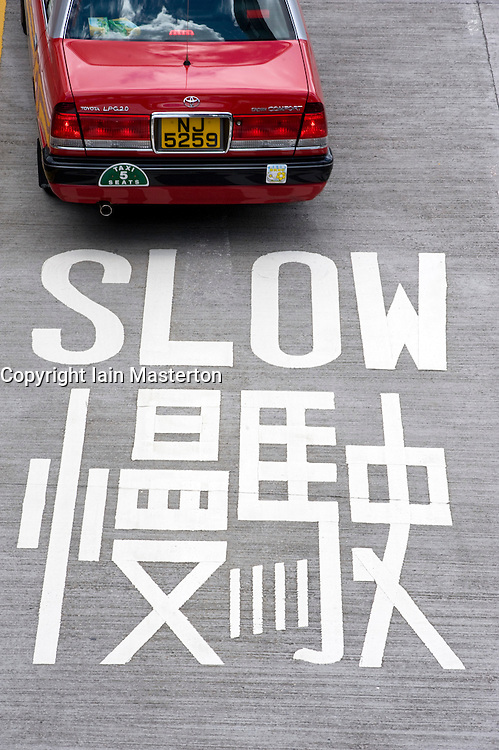 Large painted sign on road warning to drive slowly in Hong Kong China 2008