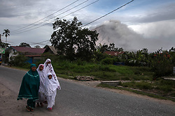 June 16, 2018 - Karo, North Sumatra, Indonesia - Indonesian Muslims make their way to a mosque an offer Eid al-Fitr prayers to mark the end of the holy fasting month of Ramadan as Mount Sinabung seen in the background at Karo, North Sumatra on June 15, 2018. Millions in Indonesia, the world's most populous Muslim country, are celebrating Eid with family reunions and feasts of traditional food after a month of prayer and fasting. (Credit Image: © Ivan Damanik via ZUMA Wire)