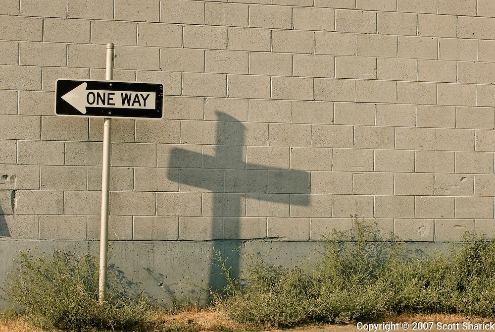 An image where the sun hits a one way sign in a way that causes a shadow on the concrete wall that takes on the shape of a crucifix. Missoula Photographer, Missoula Photographers, Montana Pictures, Montana Photos, Photos of Montana