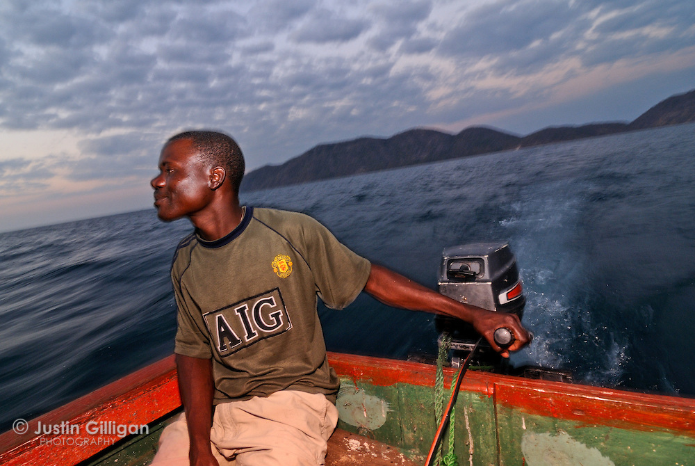 Isack Yohani navigates towards an evening of usipa fishing. Outboard motors are now a necessity to catch usipa, Lake Malawi, Malawi.