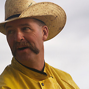 Cowboy Mike Flattery keeps his eye on the weather during a cattle roundup at the Bar B ranch near Albia, Iowa, in August of 2008.  Morning rains had made the ground sloppy.  Flattery, along with a dozen other hired hands,  roped and seperated calves from the herd for vaccinations, branding and the placement of growth stimulant implants.  The male calves were also castrated.  Owner Catherine Bay runs the operation with a herd of over 2,000 cattle.
