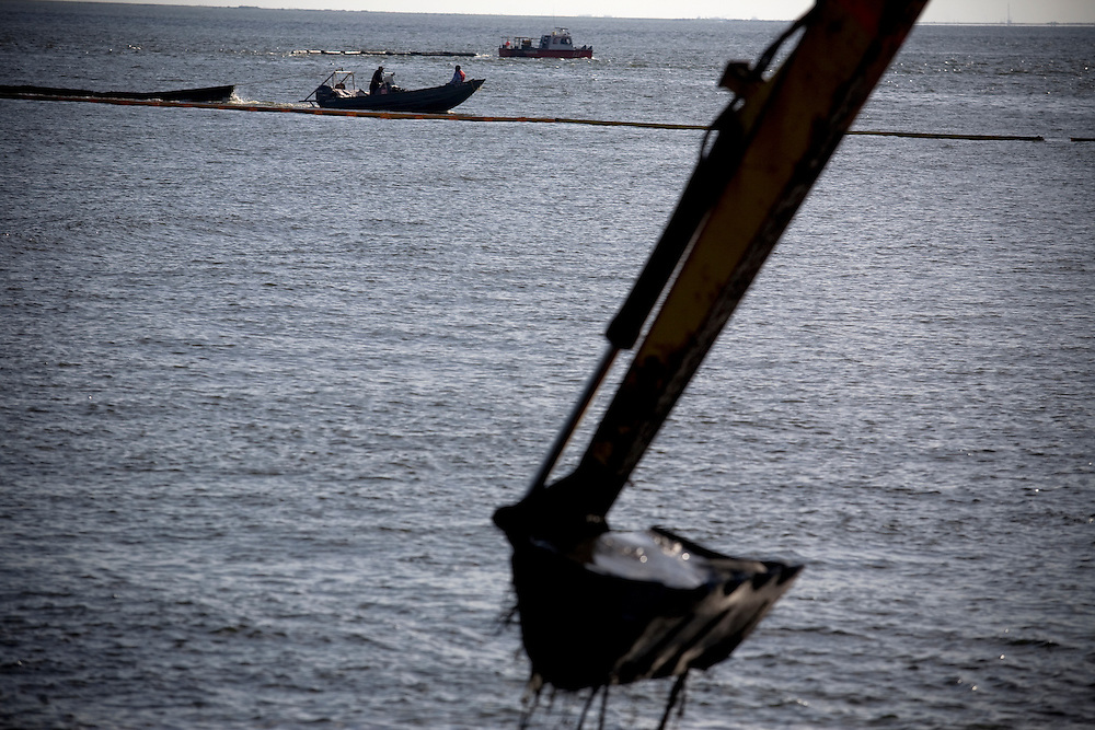 Cleanup workers lay oil barriers in the water in Grand Isle, LA on June 24, 2010 where oil has reached land.
