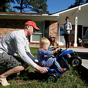 Jared Lauck, of Beaufort, helps his son Jayce Lauck, 18-month-old, wheelie up the concrete foundation of their driveway while riding in a toy four-wheeler as Jayce's mother Julie Lauck watches from the driveway at their home off of Shell Point Road on April 10, 2014.
