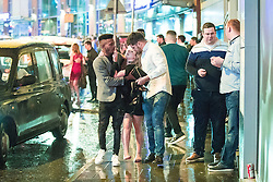 © Licensed to London News Pictures . 01/01/2017 . Manchester , UK . Two men help a woman to a taxi . People on a night out in Manchester City Centre , after midnight on January 1st 2017 . Photo credit : Joel Goodman/LNP