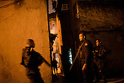 Police officers take position during an operation to occupy the Caju slum complex during a cojoint operation to install a Pacifying Police Unit (UPP) in Rio de Janeiro, Brazil, Sunday, March 3, 2013. The action is part of a program aiming to drive armed drug gangs out of Rio's slums.