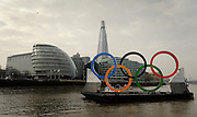 © Licensed to London News Pictures. 28/02/2012, London, UK. A view of the rings with City Hall (L) and the Shard skyscraper. Giant Olympic rings measuring 11 metres high by 25 metres wide are floated down the River Thames on a barge, marking 150 days to go to the start of the London 2012 Olympic and Paralympic Games. Photo credit : Stephen Simpson/LNP