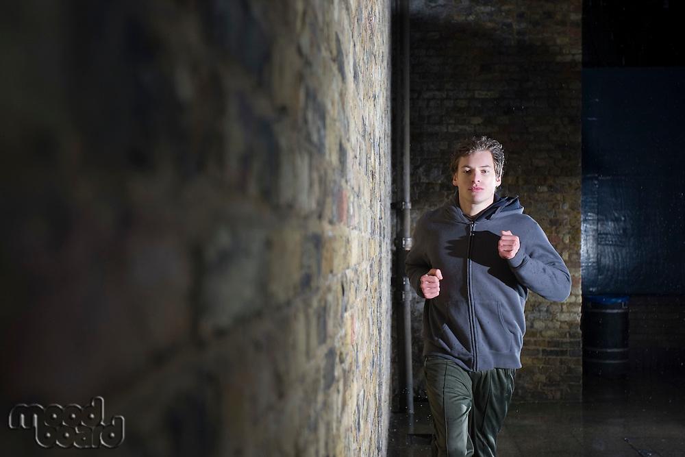 Young man jogging along side brick wall at night
