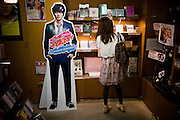 "Tokyo, September 18 2011 - Inside the shop ""Korea Plaza"", a girl  looking at concert DVDs beside a fake Korean pop star. Korean mania reached Tokyo's Korean neighborhood near Shinokubo station. For a long time Japanese ladies in their 50ies have been interested in Korean televised dramas. Recently the success of K-Pop (Korean popular music) in Japan has brought a younger population in the neighborhood."
