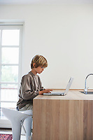 Boy using laptop at kitchen table
