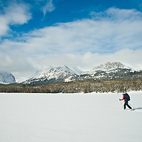 modern woman skiing across frozen lake two medicine lake winter glacier national park, montana
