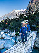 Trek across a wood footbridge near Albergue Los Cuernos, a refuge (hut) in Torres del Paine National Park, Chile, Patagonia, South America. For licensing options, please inquire.