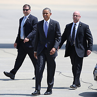 President Barack Obama walks on the tarmac, toward supporters at the Orlando International Airport on Thursday, March 20, 2014 in Orlando, Fla., enroute to the Valencia Community College West campus to speak about the role of women in the U.S. economy, as well as the challenges they still face. (AP Photo/Alex Menendez)