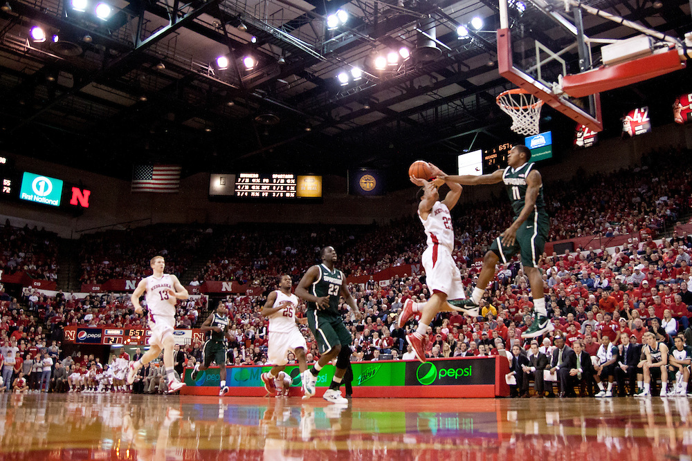 31 December 2011: Bo Spencer #23 of the Nebraska Cornhuskers with a lay up against Keith Appling #11 of the Michigan State Spartans at the Devaney Sports Center in Lincoln, Nebraska. Michigan State defeated Nebraska 68 to 55.