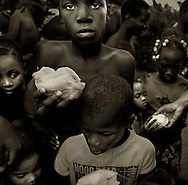 Batey50, Dominican Republic- Children line up for a food distribution offered by an American Christian mission organization. The missionary organizations are often most active between harvests when the Haitian workers of the bateyes have little means of earning enough money to support their families.   (Photo by Robert Falcetti)