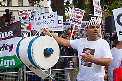 London, August 23rd, 2014. A protester displays a large roll of toilet paper made from the Israeli flag, encouraging people not to boycot such a product as hundreds of pro- Palestine protesters demonstrate outside Downing Street demanding that Britain stops arming Israel.