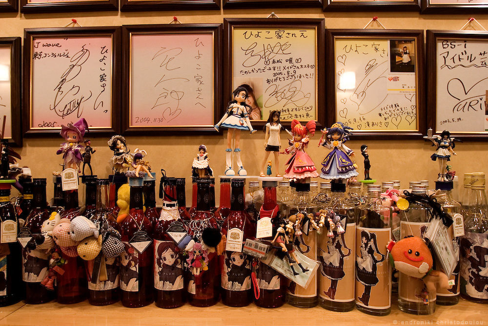 Bottles kept by customers in Maid cafe and izakaia (traditional bar-restaurant) HIYOKOYA. Their decoration is a picture of a maid on the bottle and the anime figures are typical OTAKU collection items. The messages above (In frames) are from famous customers. Comic and animation  designers, actors, musicians etc.