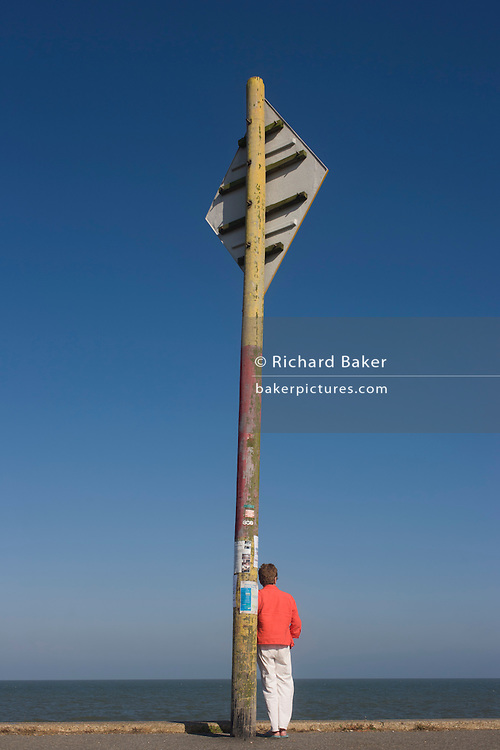 A person stands below a maritime shipping transit navigation sign at the Suffolk seaside town of Southwold, Suffolk.