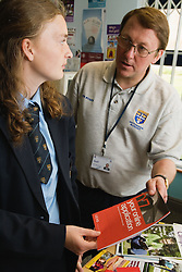 Careers advice teacher going through further education and career options with secondary school pupil,