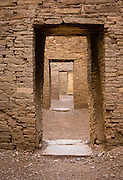 Four doorways connect rooms at Pueblo Bonito, 828-1126 AD Great House, Chaco Culture National Historical Park, New Mexico, USA. Pueblo Bonito is a monumental public building (Puebloan Great House) occupied from around 828 to 1126 AD, still standing in Chaco Canyon. The huge D-shaped complex of Pueblo Bonito enclosed two plazas with dozens of ceremonial kivas, plus 600 rooms towering 4 and 5 stories above the valley floor. The functions of this building included ceremony, administration, trading, storage, hospitality, communications, astronomy, and burial, but few living quarters. Chaco Culture NHP hosts the densest and most exceptional concentration of pueblos in the American Southwest and is a UNESCO World Heritage Site, located in remote northwestern New Mexico, between Albuquerque and Farmington. From 850 AD to 1250 AD, Chaco Canyon advanced then declined as a major center of culture for the Ancient Pueblo Peoples. Chacoans quarried sandstone blocks and hauled timber from great distances, assembling fifteen major complexes that remained the largest buildings in North America until the 1800s. Climate change may have led to its abandonment, beginning with a 50-year drought starting in 1130. Two images were combined (stitched) to increase depth of focus from near to far doorways.