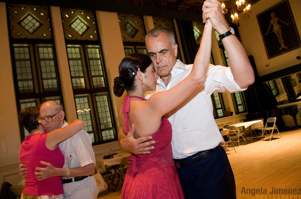 "Date: 7/10/10.Desk: ESC.Slug: LATIN DANCE.Assign Id: 30098951A..Aspiring tango dancers attend the hour-long lesson, taught by instructor Karina Romero, right, in pink dress, who is dancing with her Argentine student and friend Ramon de Oliveira (*COPY NOTE: ACCENT ON THE ""O"" IN ""RAMON""), at the beginning of the monthly Saturday night Tango event at the 92nd Street Y in New York City on July 10, 2010.  At left is student Elliott Zimmerman, 70. ..Photo by Angela Jimenez for The New York Times .photographer contact 917-586-0916"