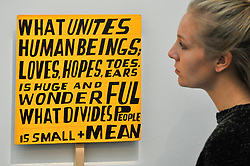 "© Licensed to London News Pictures. 12/10/2017. London, UK.  A staff member views ""What Unites Human Beings"", 2017, by Bob and Roberta Smith (Est. GBP2.5-3.5k) at a preview of artworks for the ""Art for Grenfell"" auction taking place at Sotheby's, New Bond Street, on 16 October.  Leading contemporary artists have agreed to donate works to the auction, the proceeds of which will be divided equally amongst the 158 surviving families of the Grenfell Tower fire by the Rugby Portobello Trust charity. Photo credit : Stephen Chung/LNP"