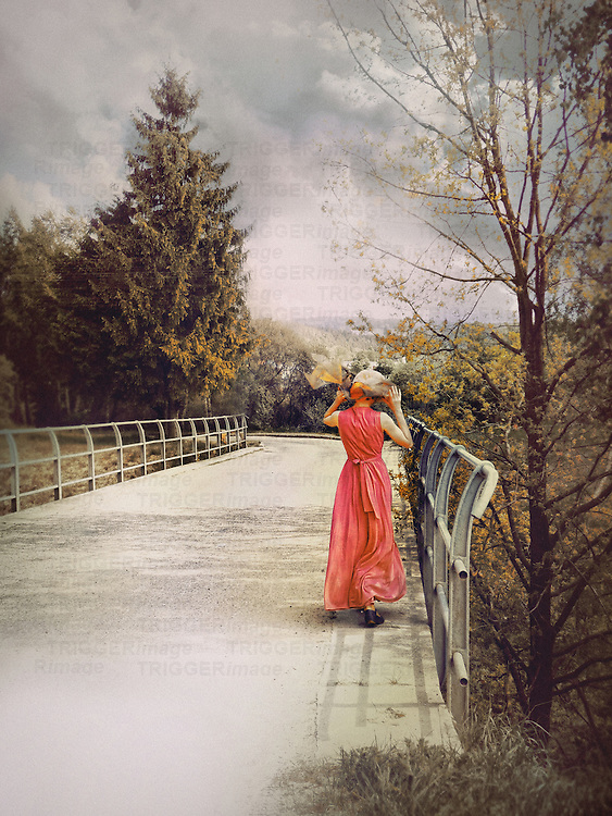 A woman in a red dress and a summer hat, walking down a path on a bridge among trees.