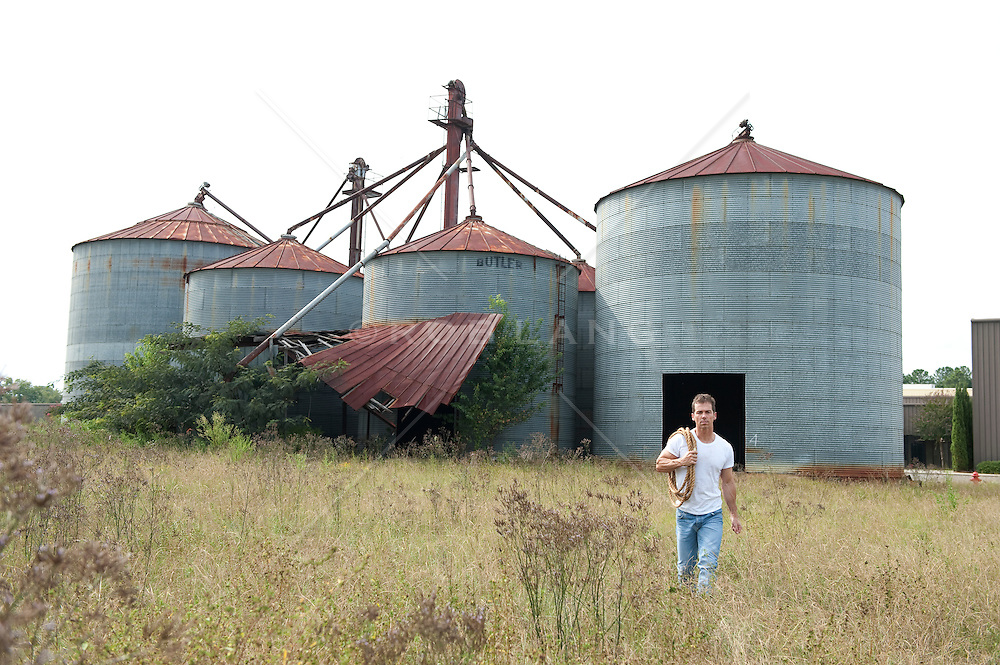 man outdoors walking in a field near an abandoned grain factory