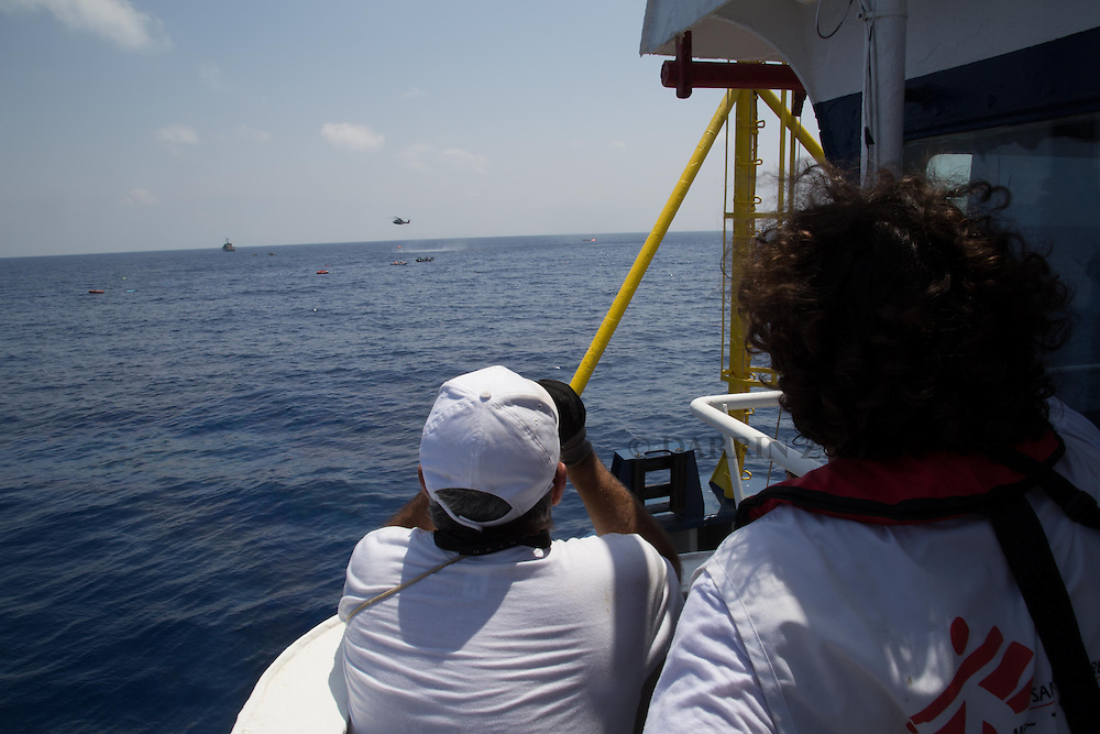Medecins san Frontiere (MSF) Field coordinator Juan and first officer Porfirio follow the rescue operation involving ships and sea rescue helicopters, scanning the area to spot survivors in the water where a boat carrying migrants  capsized and sank with many feared drowned off the coast of Libya August 5, 2015.  A boat packed with up to 700 African migrants capsized in the Mediterranean Sea off the coast of Libya on Wednesday and many were feared dead, officials and aid agencies said. <br /> REUTERS/Marta Soszynska/MSF/ Handout<br /> NO ARCHIVE. NO COMMERCIAL USE. NO SALES