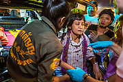 "30 NOVEMBER 2012 - BANGKOK, THAILAND:  Volunteer medics with the Ruamkatanyu Foundation help a woman who collapsed on a Bangkok street during a Friday night shift. The Ruamkatanyu Foundation was started more than 60 years ago as a charitable organisation that collected the dead and transported them to the nearest facility. Crews sometimes found that the person they had been called to collect wasn't dead, and they were called upon to provide emergency medical care. That's how the foundation medical and rescue service was started. The foundation has 7,000 volunteers nationwide and along with the larger Poh Teck Tung Foundation, is one of the two largest rescue services in the country. The volunteer crews were once dubbed Bangkok's ""Body Snatchers"" but they do much more than that now.   PHOTO BY JACK KURTZ"