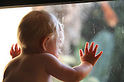 Baby girl looks out through a dirty window
