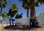 "Santiago Ibarra works with a landscape crew to remove grass and install low water use ""xeroscape"" landscaping in the Smoke Ranch neighborhood of Las Vegas, Nevada.  The homeowners association decided to make the change in response to the huge increases in water rates.  Wednesday, April 21, 2004."