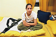 Female soldier in her bedroom with rifle and teddy bear, Israel. Portrait by Debbie Zimelman, Modiin, Israel