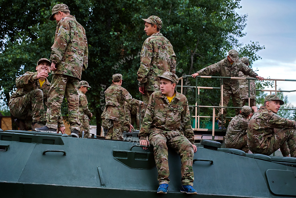 Youngsters participating to the ultra-nationalistic Azovets children's camp are playing around military vehicles, in exposition on site on the banks of the Dnieper river, in Kiev, Ukraine's capital.