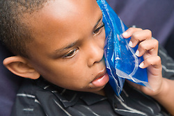 Boy holding ice pack to cheek looking sad,
