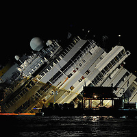 ISOLA DEL GIGLIO, ITALY - SEPTEMBER 16:  The wreckage of the Costa Concordia is seen in the evening of the day when the ship is readied for a salvage operation on September 16, 2013 in Isola del Giglio, Italy. Work begins today to right the stricken Costa Concordia vessel, which sank on January 12, 2012. If the operation is successful, it will then be towed away and scrapped. The procedure, known as parbuckling, has never been carried out on a vessel as large as Costa Concordia before.  (Photo by Marco Secchi/Getty Images)
