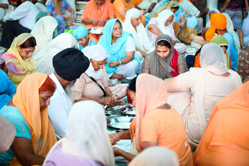 Volunteers peel garlic at a Sikh kitchen in Amritsar,Punjab,India.The sikh kitchen at the Golden temple provides ten of thousands of free meals on a daily basis. The main work force at the Sikh kitchen is made of Sikh volunteers.