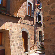 Stone archway, door, steps and windows of home in Civita di Bagnoregio, Italy<br />
