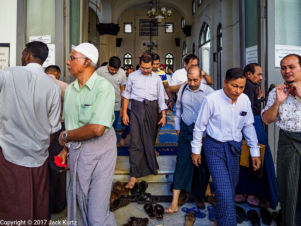 "24 NOVEMBER 2017 - YANGON, MYANMAR: Men leave Mogul Shiah Mosque in Yangon after Friday midday prayers. Many Muslims in overwhelmingly Buddhist Myanmar feel their religion is threatened by a series of laws that target non-Buddhists. Under the so called ""Race and Religion Protection Laws,"" people aren't allowed to convert from Buddhism to another religion without permission from authorities, Buddhist women aren't allowed to marry non-Buddhist men without permission from the community and polygamy is outlawed. Pope Francis is to arrive in Myanmar next week and is expected to address the persecution of the Rohingya, a Muslim ethnic minority in western Myanmar. Some Muslims and Christians are concerned that if the Pope's comments take too strong of pro-Rohingya stance, he could exacerbate religious tensions in the country.  PHOTO BY JACK KURTZ"