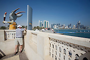 "Asian Games 2006 mascot ""Orry"" (an oryx antelope) carrying the torch in front of the skyline of Western Corniche."
