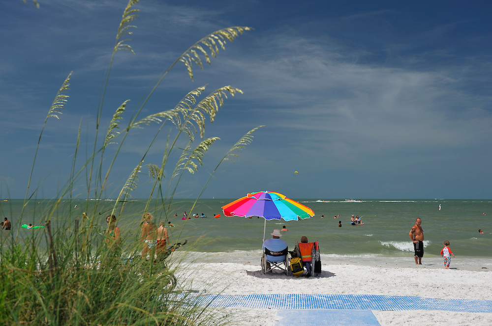 People with sund umbrealla on sand beach, Fort Myers Beach, Florida, USA