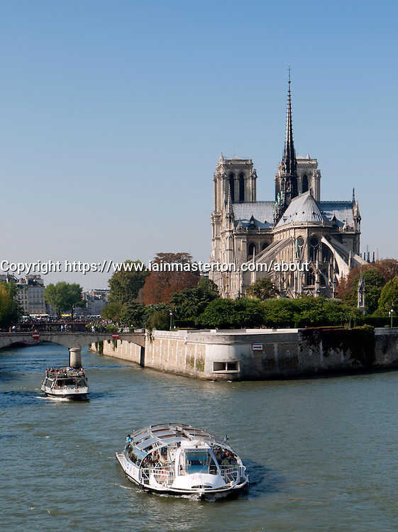 Tourists boats on River Seine with Notre Dame Cathedral in Paris France
