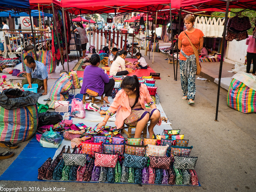 "11 MARCH 2016 - LUANG PRABANG, LAOS:  A tourist walks through a handicraft market in Luang Prabang. Luang Prabang was named a UNESCO World Heritage Site in 1995. The move saved the city's colonial architecture but the explosion of mass tourism has taken a toll on the city's soul. According to one recent study, a small plot of land that sold for $8,000 three years ago now goes for $120,000. Many longtime residents are selling their homes and moving to small developments around the city. The old homes are then converted to guesthouses, restaurants and spas. The city is famous for the morning ""tak bat,"" or monks' morning alms rounds. Every morning hundreds of Buddhist monks come out before dawn and walk in a silent procession through the city accepting alms from residents. Now, most of the people presenting alms to the monks are tourists, since so many Lao people have moved outside of the city center. About 50,000 people are thought to live in the Luang Prabang area, the city received more than 530,000 tourists in 2014.      PHOTO BY JACK KURTZ"