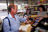 Postman hands letters to a shopkeeper on his walk ......