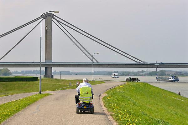 Nederland, Beneden Leeuwen, Waal, 7-5-2013Druk verkeer van binnenvaartschepen op de waal, rijn, vooral op en neer het duitse ruhrgebied en de haven van rotterdam. Een oudere man rijdt op een scootmobiel over de dijk.Foto: Flip Franssen