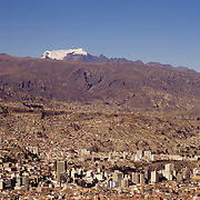 The city of La Paz & the snow capped Mount Illimani seen from El Alto. Bolivia.