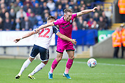 Rochdale defender Rhys Norrington-Davies challenged by Bolton Wanderers midfielder Dennis Politic during the EFL Sky Bet League 1 match between Bolton Wanderers and Rochdale at the University of  Bolton Stadium, Bolton, England on 19 October 2019.
