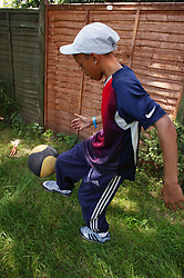 Young teenager playing with a football in the garden,
