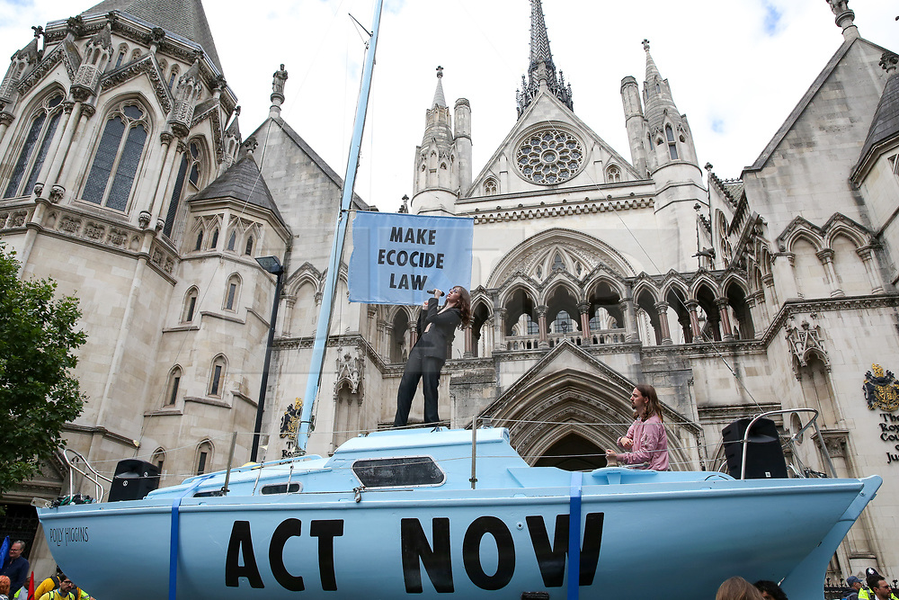 © Licensed to London News Pictures. 15/07/2019. London, UK. Jessica Winter sings on a boat placed outside Royal Courts of Justice. <br /> Hundreds of Extinction Rebellion climate change activists protests outside the Royal Courts of Justice demanding the legal system take responsibility in the climate change crisis, and ensure the safety of future generations by making ecocide law. The environmental group is staging similar protests in  Leeds, Cardiff, Glasgow, Bristol, Norwich and other cities around the country. Photo credit: Dinendra Haria/LNP