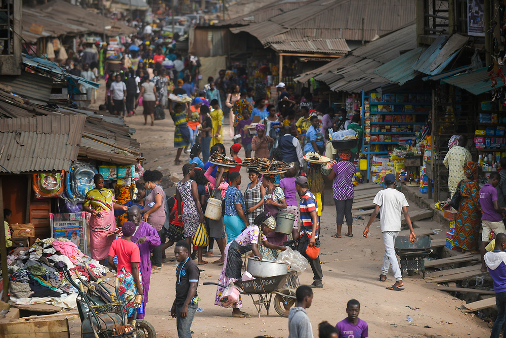INDIVIDUAL(S) PHOTOGRAPHED: N/A. LOCATION: Lagos Road Market, Benin City, Edo State, Nigeria. CAPTION: People walk through a commercial market near the business and financial hub of Benin City in Nigeria's Edo State.